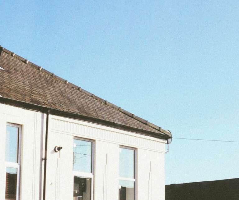 Photo d'une maison avec une toiture de bardeaux foncés